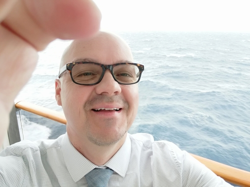 Selfie of Sean Zdenek taken on the balcony of a cruise ship with the Atlantic Ocean in the background