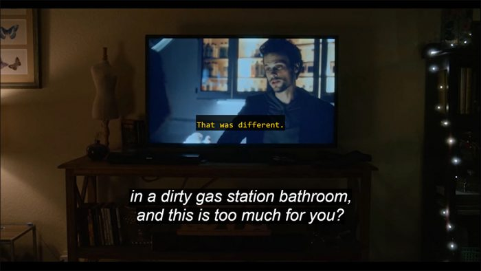 "A frame from Horse Girl showing a TV screen, which includes a yellow caption, ""That was different."" At the bottom of the frame is a second caption track in white letters: ""in a dirty gas station bathroom, and this is too much for you?"""